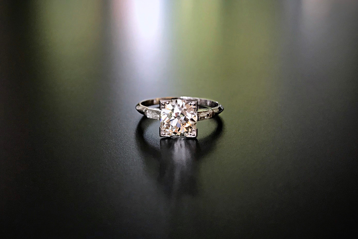 A Stunning Vintage Solitaire Diamond Ring Early round brilliant cut diamond raised in a square frame Small baguette cut diamond horizontally set to the shoulder Platinum Total diamond weight: 1.62cts Colour: H Clarity: SI