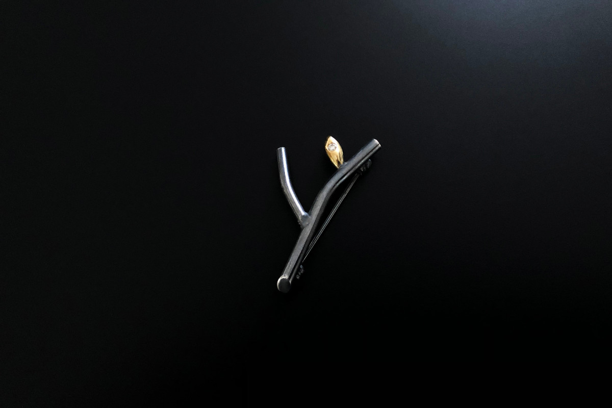 Inspired by the resilient nature of the human spirit, The Hope Pin reflects renewal and hope for the future. Designed and hand-crafted by Studio Manager, Dat Van. Oxidised silver and 18k gold. Diamond weight: 0.10cts. Approximately 37 x 20mm