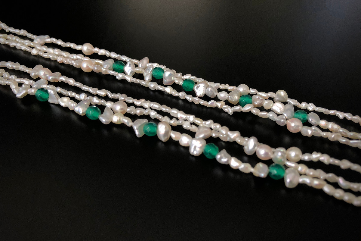 A Delightful Akoya Keshi Pearl and Green Agate Necklace Comprising three strands of Akoya Keshi pearls measuring 1.5 - 2.5mm.  Interspaced with faceted green agate beads Sterling silver clasp. Total length 850mm.