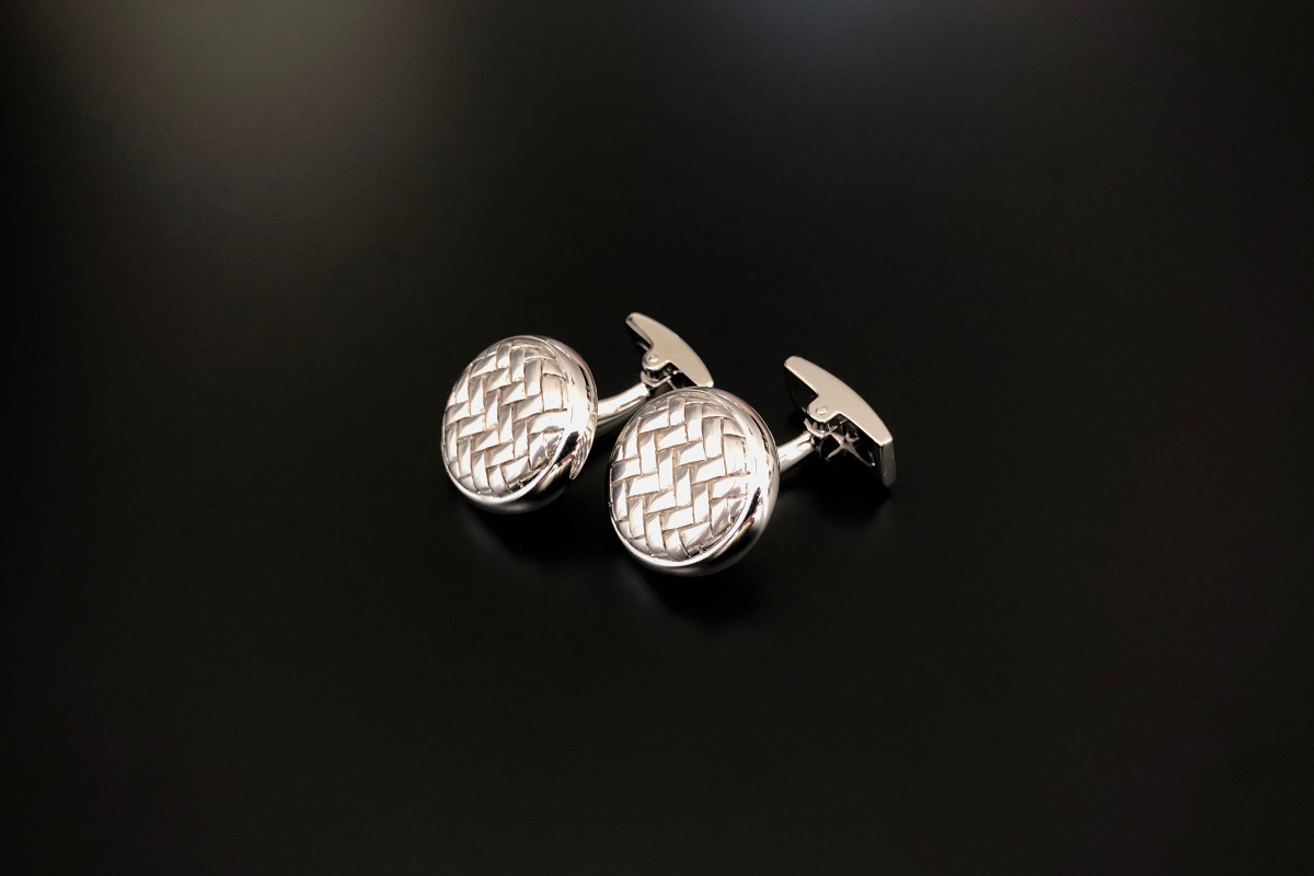 Woven mesh cufflinks in raised disc form with convex rectangular panel to the opposing end. Sterling Silver.