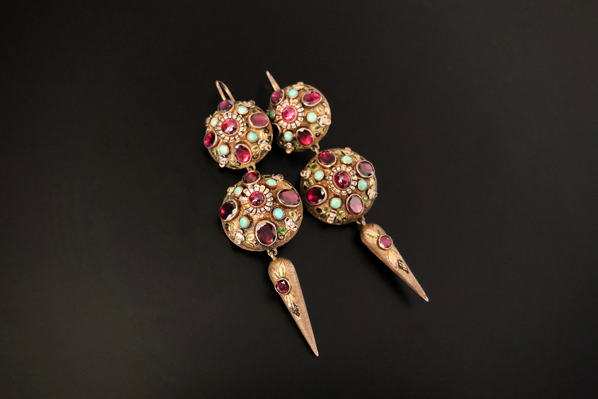 A Fabulous Pair of Austro Hungarian Earrings Comprising two graduated domed panels and an elongated drop set with foiled back garnets and turquoise. Having enamel highlights throughout Silver gilt Circa 1900