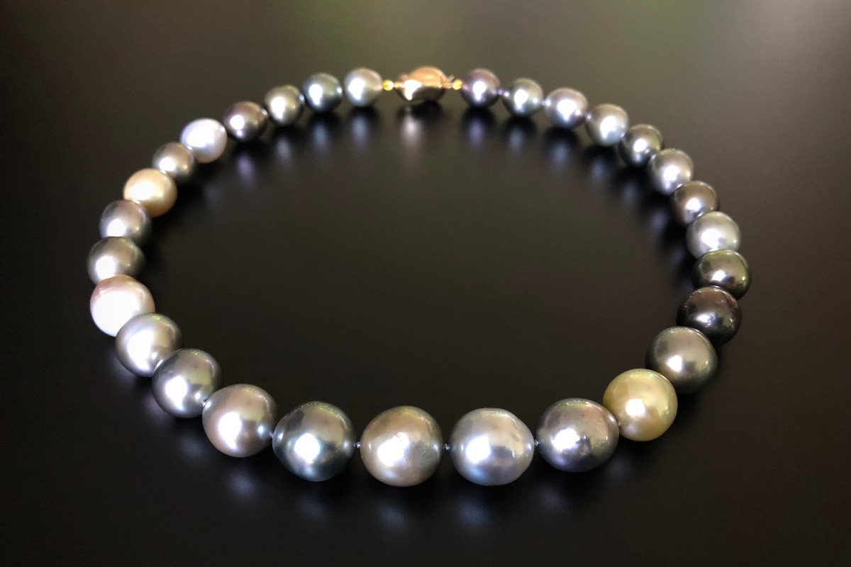 Tahitian Multi-Colour Baroque Pearl Necklace. Comprising twenty nine graduated Baroque pearls of beautiful lustre with varying hues of white, gold and silver measuring 11 x 17mm. Baroque gold clasp in 18ct gold. Total length: 460mm.