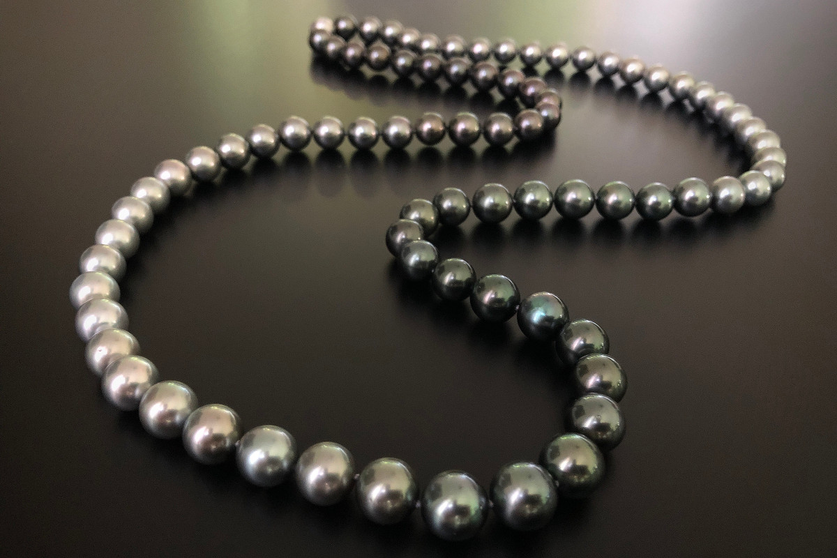Tahitian Pearl Necklace with Fading Hues. Comprising eighty round Tahitian pearls with beautiful lustre and alternating fading hues, individually knotted to a brushed 18ct white gold ball clasp. Total length: 970mm.