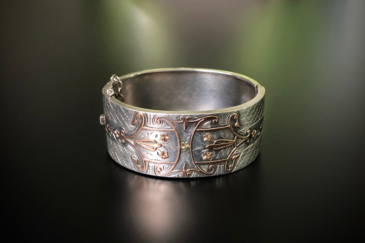 Silver and Gold Cuff Bangle Oval hinged form Floral and scroll decoration with applied rose gold detail and engraved chevron and foliate highlights Engraved to reverse F Demasenier Sliding tongue clasp and safety chain Victorian Circa 1890