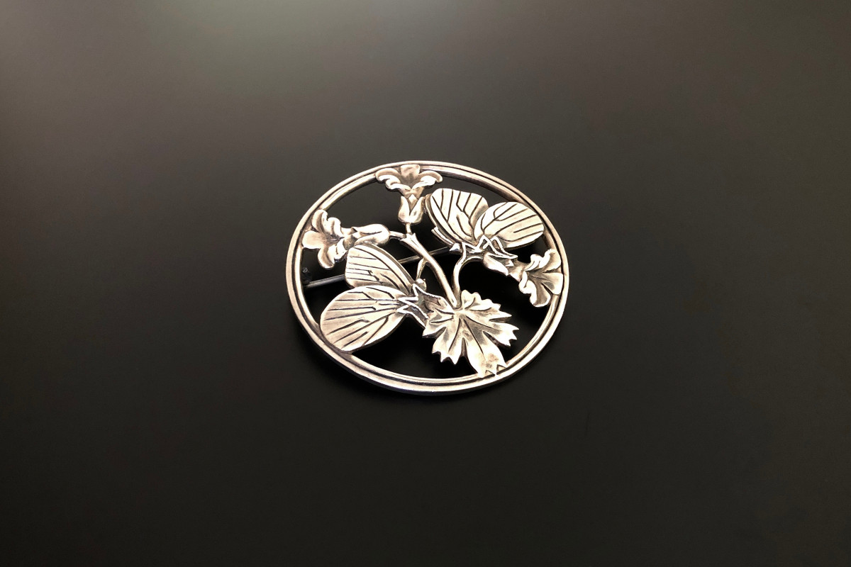 Sterling Silver Brooch by Georg Jensen Designed by Arno Malinowski Circular pierced form with stylised butterflies and flowers Sterling silver Reference N.256 Total weight: 25.05gms Total length: 53mm