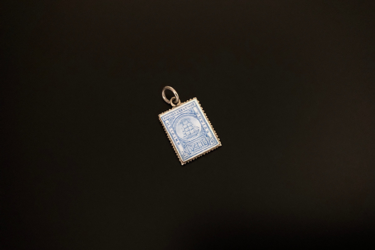 An Unusual Silver Gilt and Enamel Pendant Miniature British Guiana postage stamp  Blue and white enamel Silver Total weight: 62.15ms 15 x 10mm