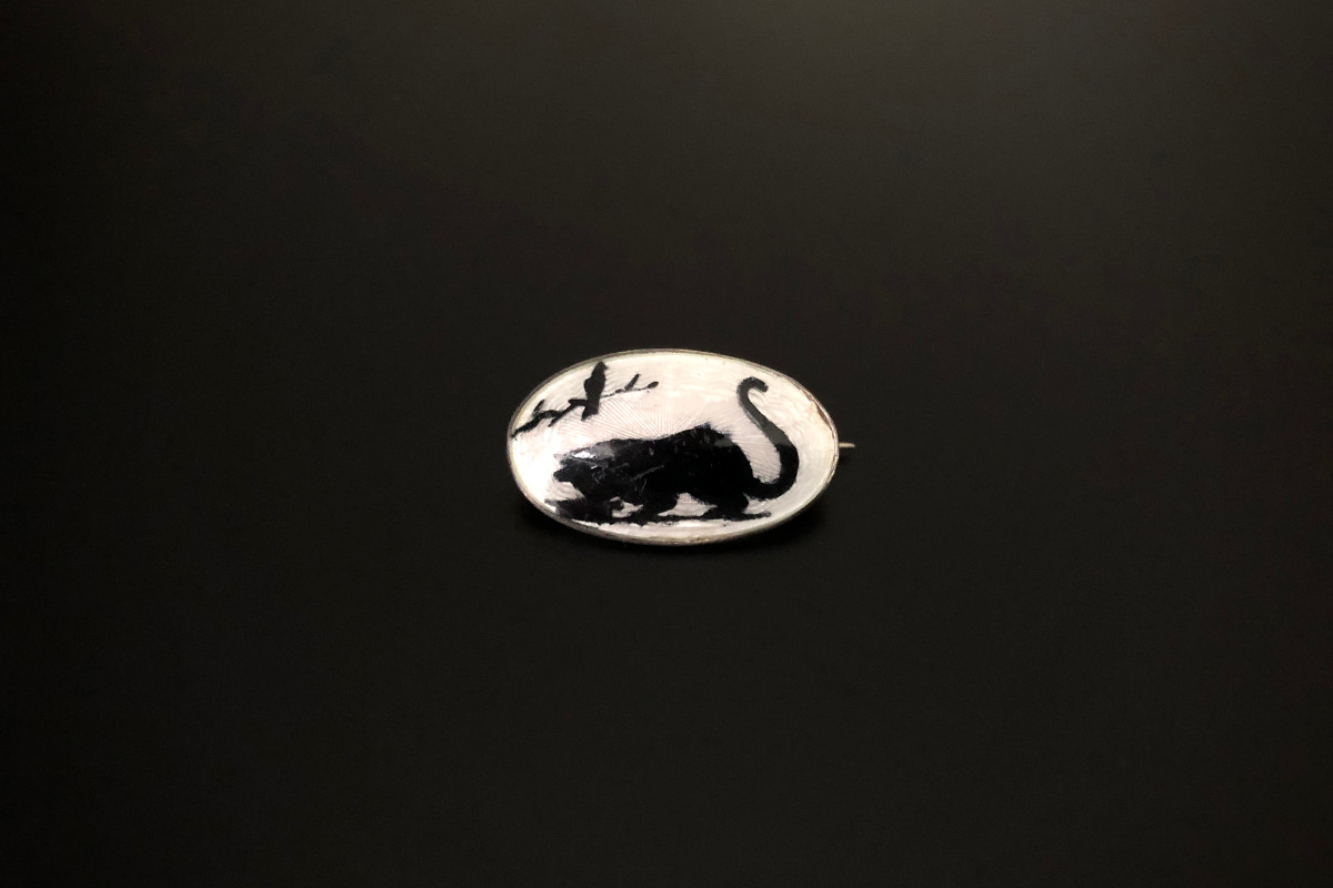 A Whimsical Sterling Silver and Enamel Brooch Oval form Depicting a cat silhouette Black and white enamel Sterling silver Total weight: 3.5gms Total length: 25 x 14mm