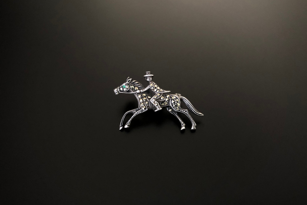 A Smart Sterling Silver and Marcasite Brooch Modelled as a horse and rider Green paste set eye Sterling silver Total weight 4.50gms Total length: 35mm x 28mm