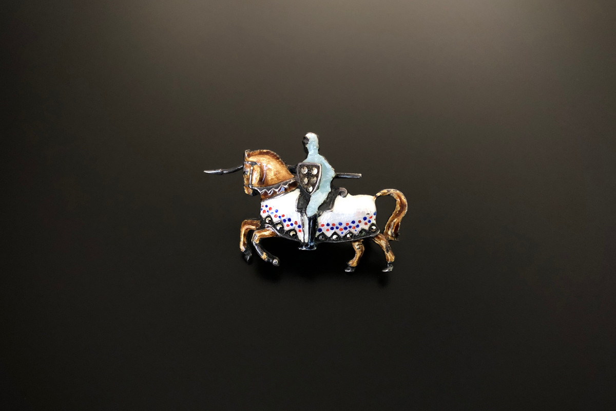 A Dreamy Silver, Enamel and Marcasite Brooch Modelled as a knight riding a horse Brown, blue, white, red and black enamel Silver Hand set Total weight: 8.60gms Total length: 39mm x 15mm