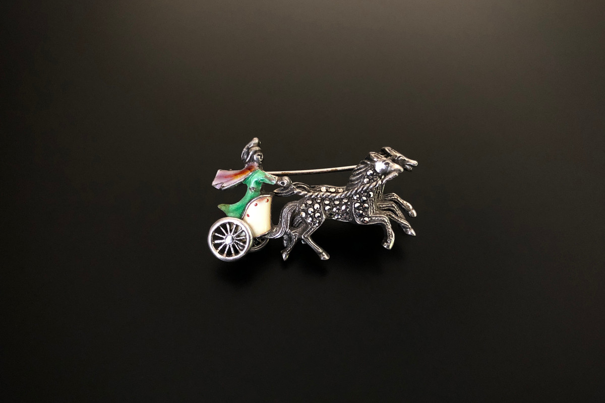 A Sensational Sterling Silver, Enamel and Marcasite Brooch  Modelled as a centurion riding a chariot Cream, green, oriole and red enamel Sterling silver Circa 1940 Total weight: 9.80gms Total length: 40mm x 20mm