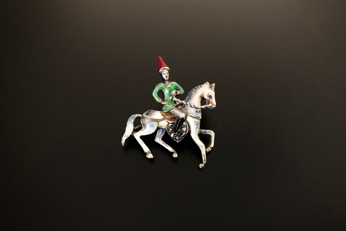A Delightful Sterling Silver, Enamel and Marcasite Brooch Modelled as a man riding a horse White, grey, green, red and black enamel Sterling silver Early 1900s Total weight: 8.35gms Total length: 31 x 40mm