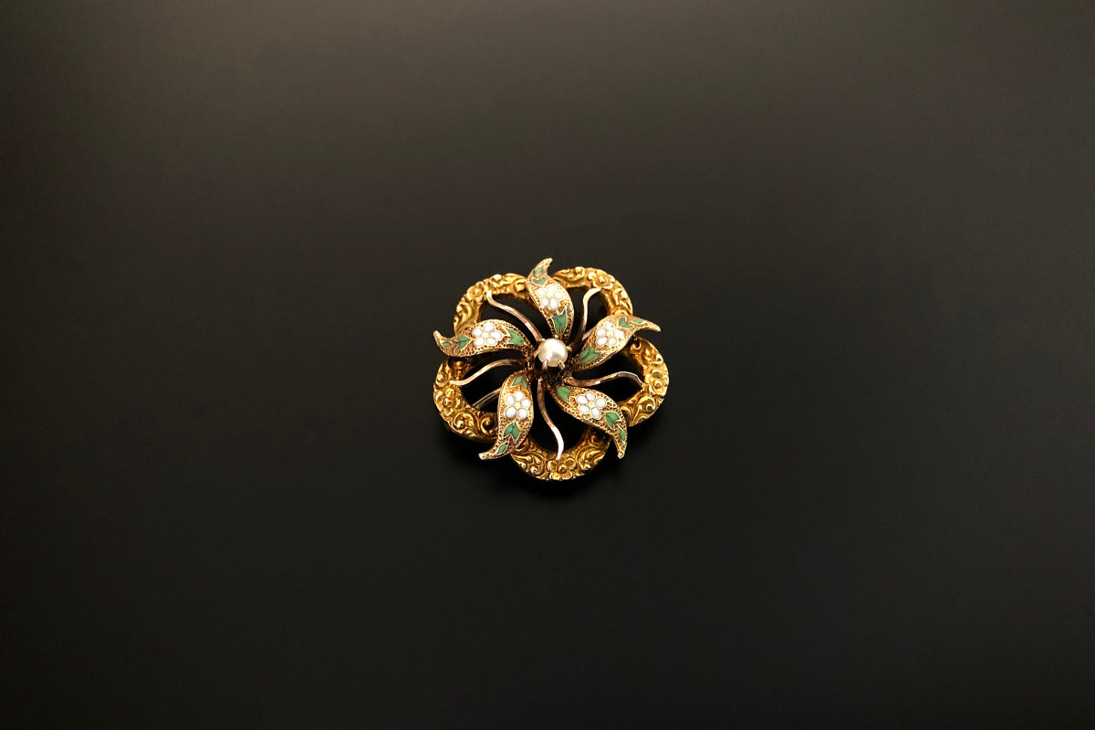 A Dainty Gold, Enamel and Pearl Brooch Pierced form Centred with a flower, each petal enamelled with small white flowers and green leaves  Having a chased border 14ct yellow gold Total weight: 3gms Diameter: 22mm