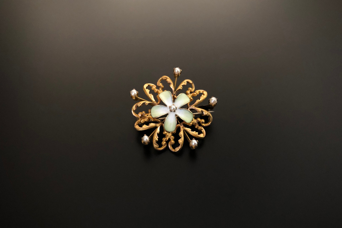 A Lovely Gold, Enamel and Pearl Brooch Central delicate flower in pale green and white enamel Within a pierced gold floral frame Highlighted by small seed pearls 14ct yellow gold?? Total weight: 4.1gms Diameter: 25mm