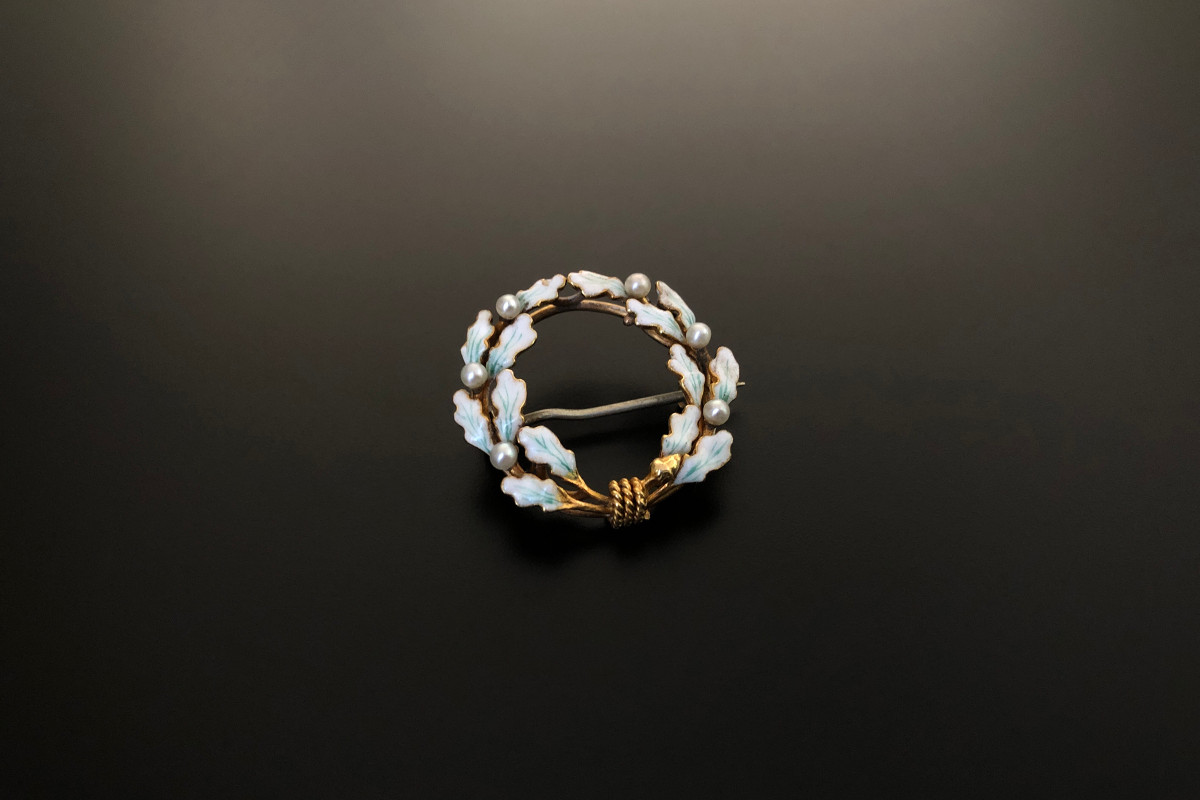 A Superb Gold, Enamel and Pearl Garland Brooch by Krementz Circular pierced form Interwoven oak leaved enamelled in white and green Highlighted by seed pearls Tied with delicate gold rope and finished with an acorn 14ct yellow gold Total weight: 2.85gms Diameter: 23mm