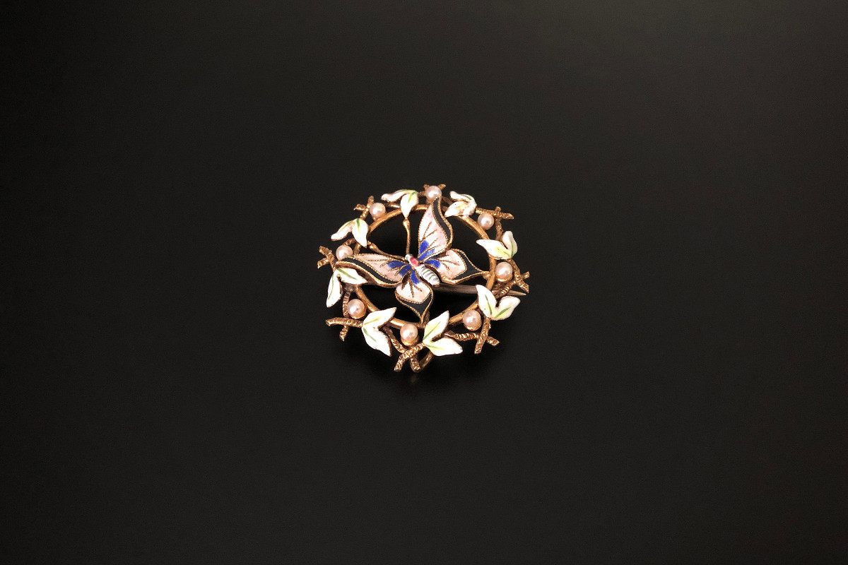 An Exquisite Gold, Enamel and Pearl Garland Brooch Circular pierced form  Centrally set with a butterfly enamelled in pink, white, blue and black Framed by green and white enamelled leaves and highlighted by small pearls 14ct??? Gold Total weight: 3.4gms Diameter: 25mm