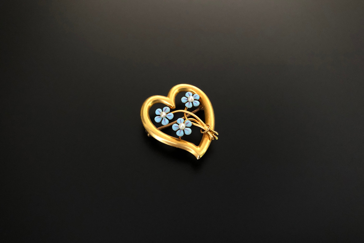 A Divine Gold and Enamel Honeymoon Pin by Krementz Stylised pierced heart Centrally set with a bouquet of blue enamel forget me knots 14ct yellow gold Total weight: 2.3gms Total length: 24mm