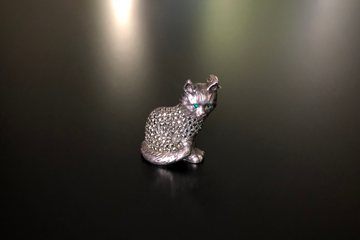 A Delightful Sterling Silver and Marcasite Cat Brooch Stylised form with the tail wrapped around the body Green paste set eyes Sterling Silver German Total weight: 9.4gms Total length: 30mm