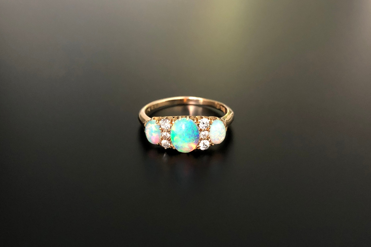 A Beautiful Opal and Diamond Ring Featuring three oval solid white opals cut en cabochon of graduated size Interspaced with small old cut diamonds  18ct yellow gold Total diamond weight: 0.16cts Colour: I Clarity: SI Total weight: 2.00gms