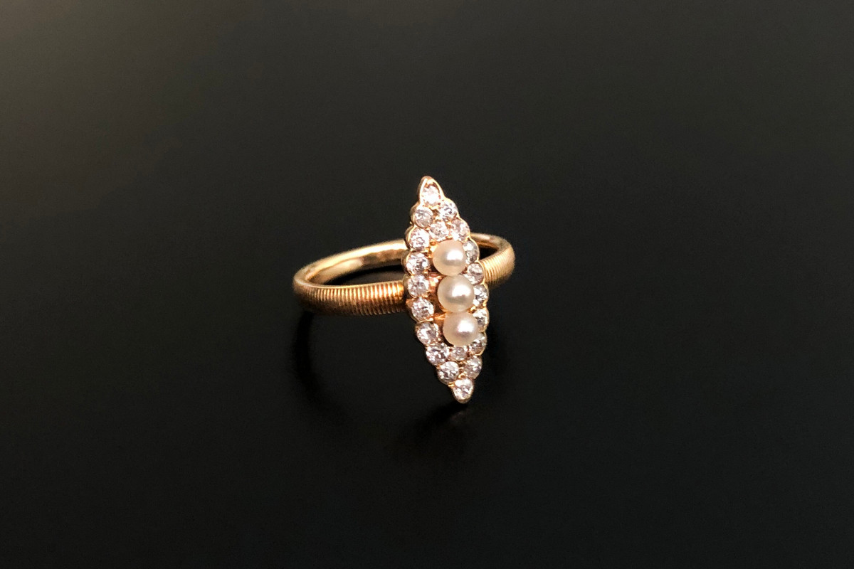 A Dainty Diamond and Pearl Plaque Ring Marquise form Centred with three small natural pearls Surrounded by twenty old cut diamonds Finely etched band 18ct yellow gold Total diamond weight: 0.45cts Colour: G Clarity: VS Total weight: 2.55gms Edwardian Circa 1900