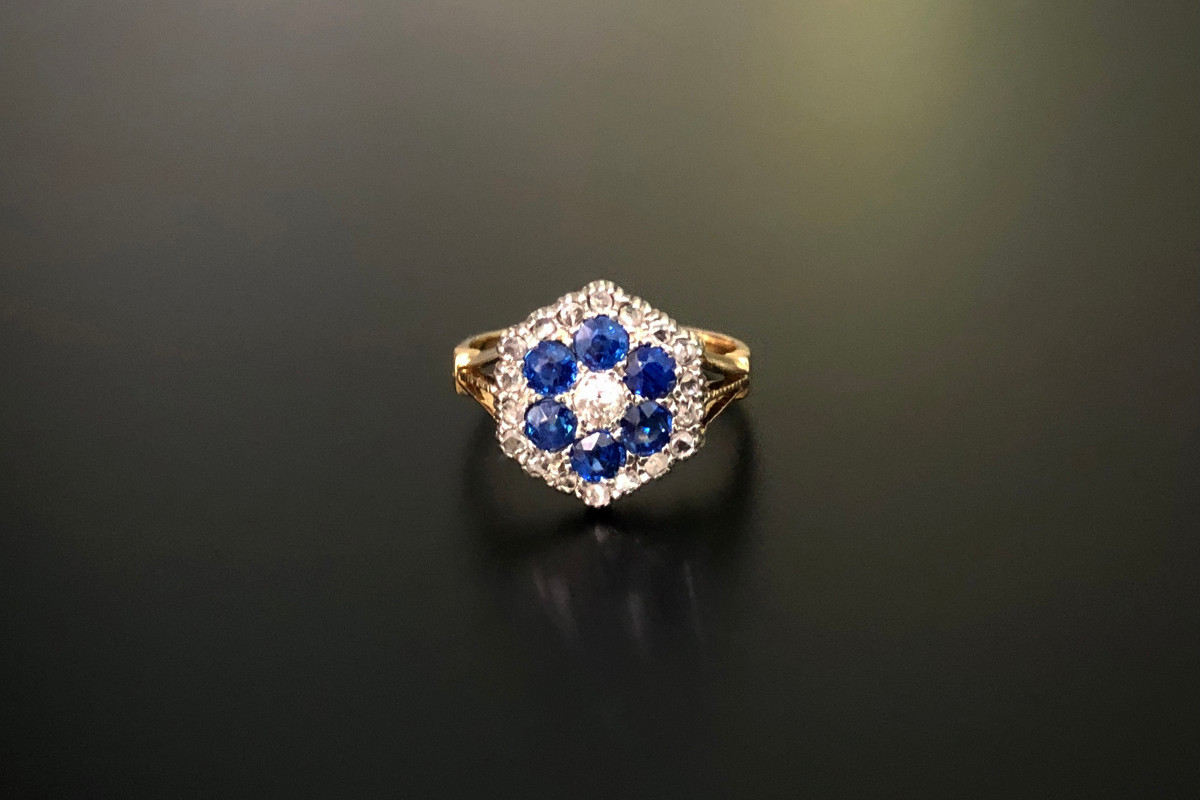 A Pretty Sapphire and Diamond Cluster Ring Central old European cut diamond surrounded by six round sapphires Having a hexagonal border of old cut diamonds  18ct gold Total diamond weight: 0.40cts Colour: H Clarity: SI Total sapphire weight: 0.85cts Total weight: 2.15gms