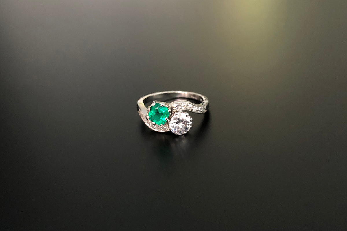 A Beautiful Diamond and Emerald Moi et Toi Ring Early round brilliant cut diamond offset to a cushion cut emerald  Coronet frames Single cut diamond detail to the curved shoulders Platinum Principal diamond: 0.51cts Emerald weight: 0.30cts Total diamond weight: 0.61cts Total weight: 2.40gms
