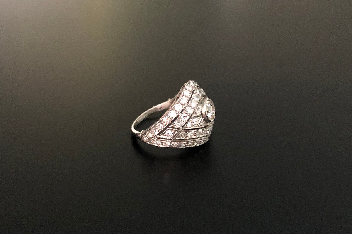 A Fabulous Diamond Plaque Ring Domed lozenge form Central old European cut diamond surrounded by three rows of single cut diamonds finely grain set in a saw pierced tapered frame Platinum Centre diamond: 0.70cts  Total diamond weight: 2.50cts Colour: G-H Clarity: VS-SI Total weight: 4.85gms Art Deco Circa 1930