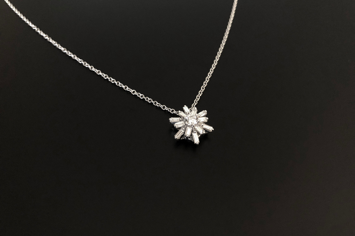A Divine Diamond Star Cluster Pendant Centrally set with a round brilliant cut diamond  Surrounded by radiating baguette cut diamonds Total diamond weight: 0.56cts Colour: G Clarity: SI 10mm x 12mm Total weight: 2.94gms Adjustable cable link chain: 40-50cm 18ct white gold