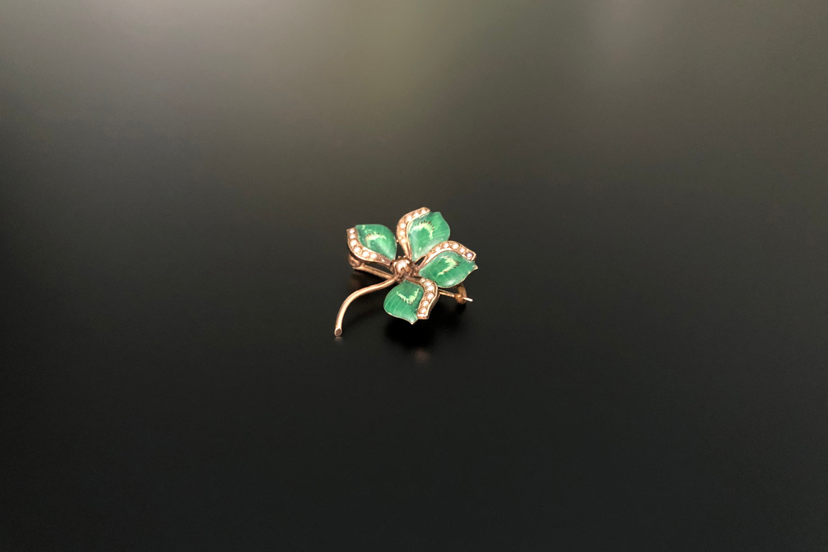 A Dainty Four Leaf Clover Gold, Enamel and Seed Pearl Brooch Matt green enamel petals, each set with a row of seed pearls Finished with an additional seed pearl to the centre 14ct yellow gold Circa 1890 American Total weight: 3gms