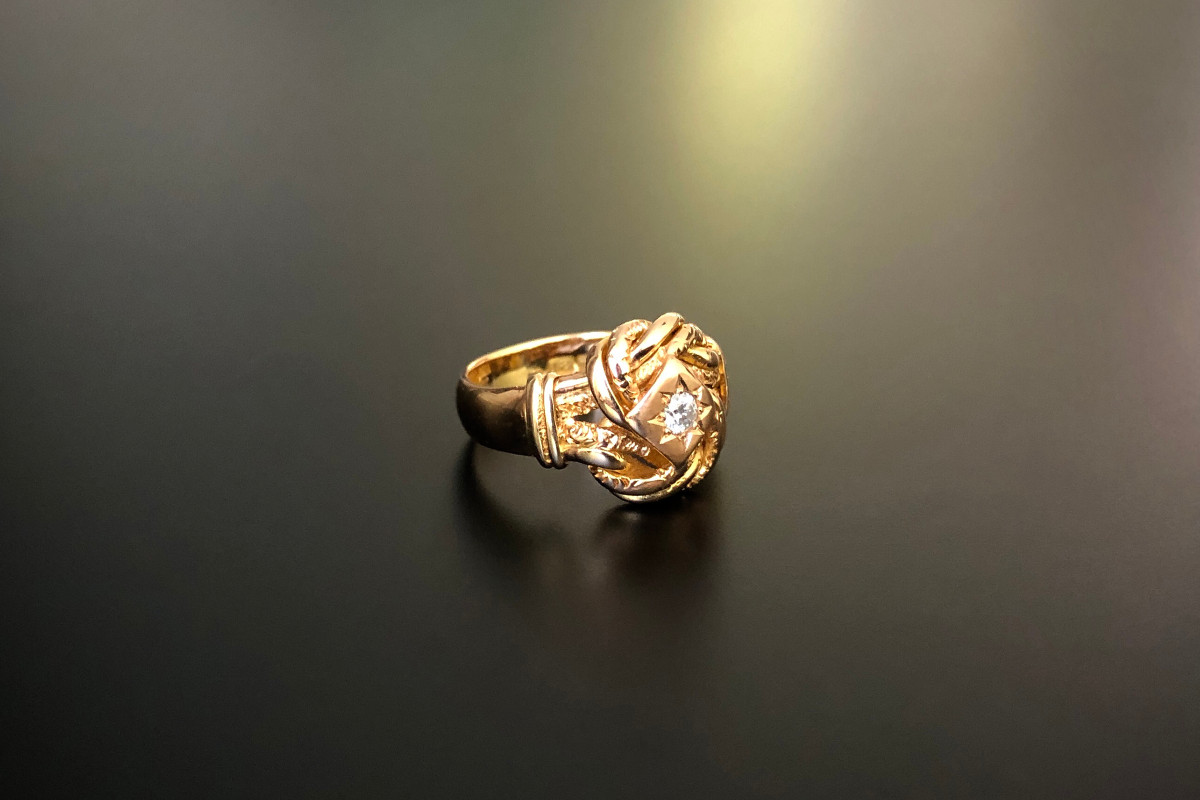 A Bold Gold and Diamond Knot Ring Early round brilliant cut diamond set within an elaborate knot with polished and chased finish 18ct gold Hallmarked Birmingham 1912 Diamond weight: 0.20cts Total weight: 4.45gms