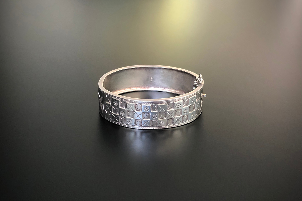 A Classic Sterling Silver Bangle Oval hinged form Chequerboard design with cross and floral motifs Safety chain Sterling silver Hallmarked Chester 1887 Total weight: 16.1gms