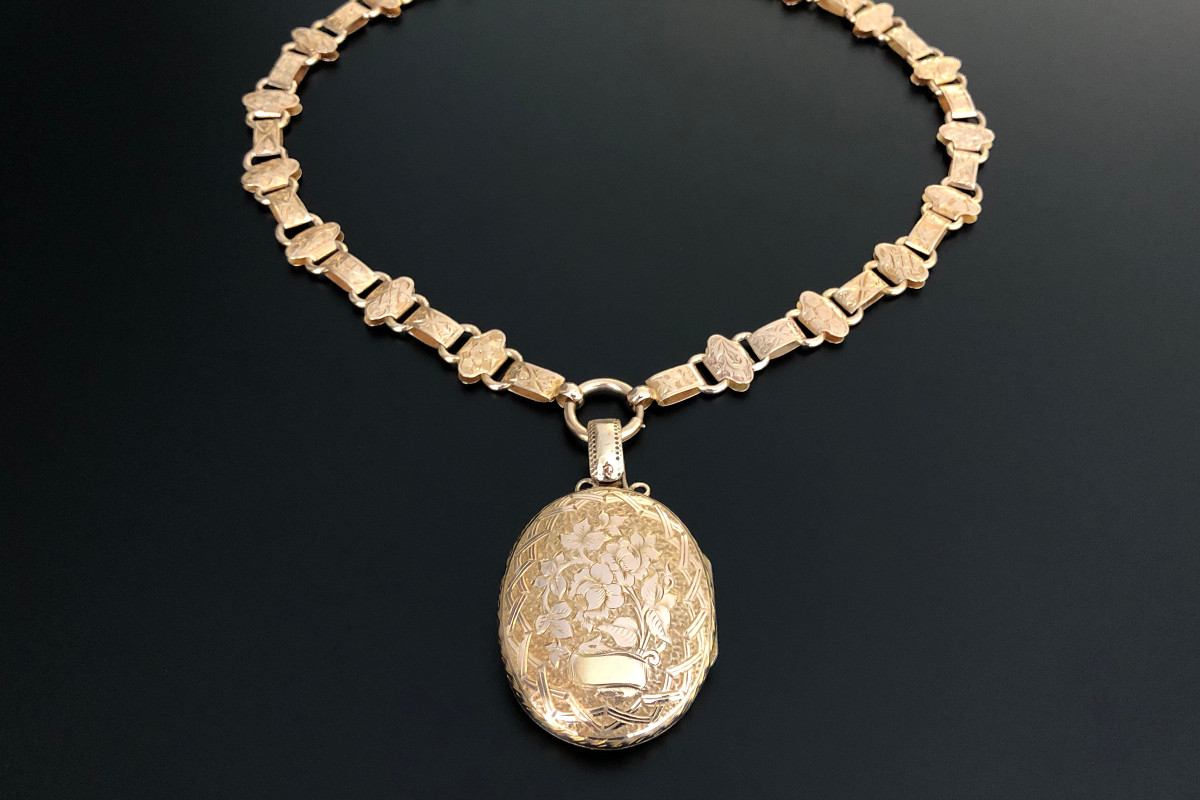 A Sensational Gold Locket and Collar Oval hinged form with elaborate engraved floral decoration Suspended from a collar comprising rectangular and quatrefoil links with engraved foliate decoration 9ct gold Total weight: 25.1gms Total length: 515mm Victorian Circa 1880
