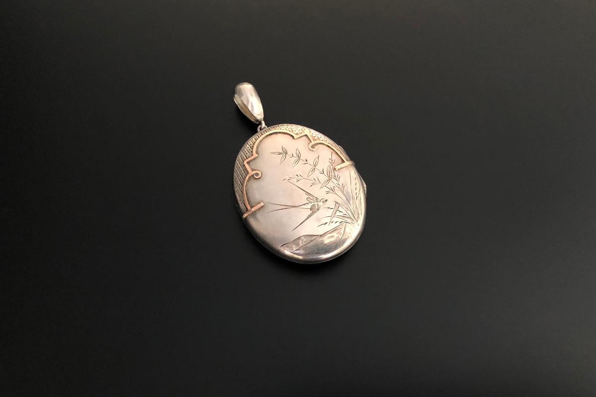 An Outstanding Silver and Gold Aesthetic Movement Locket Oval hinged form Depicting a bird amongst foliage  Highlights by rose gold border and engine turned detail Total weight: 22.75gms Total length: 85 x 45mm