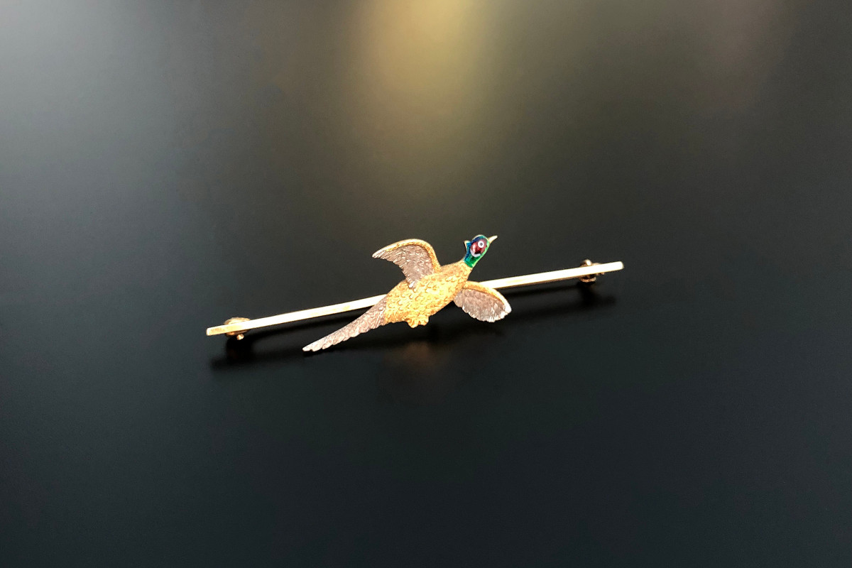 Gold and Enamel Pheasant Brooch  The bird in flight finely crafted yellow and white gold with green, red, blue and white enamel Set on a fine bar brooch 18ct and 15ct gold Total weight: 4.38gms Total length: 70mm Edwardian Circa 1910