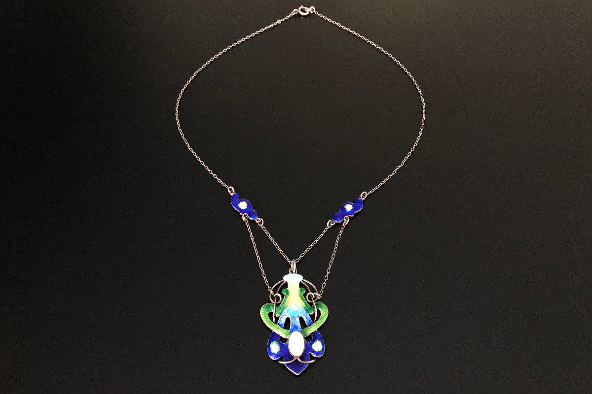 A Superb Silver, Enamel and Pearl Necklace Naturalistic scroll form Highlighted with blue, green, yellow and white enamel Centred with a blister pearl Suspended from fine trace chain Sterling silver Total weight 11.6gms Total length: 580mm Art Nouveau Circa 1910