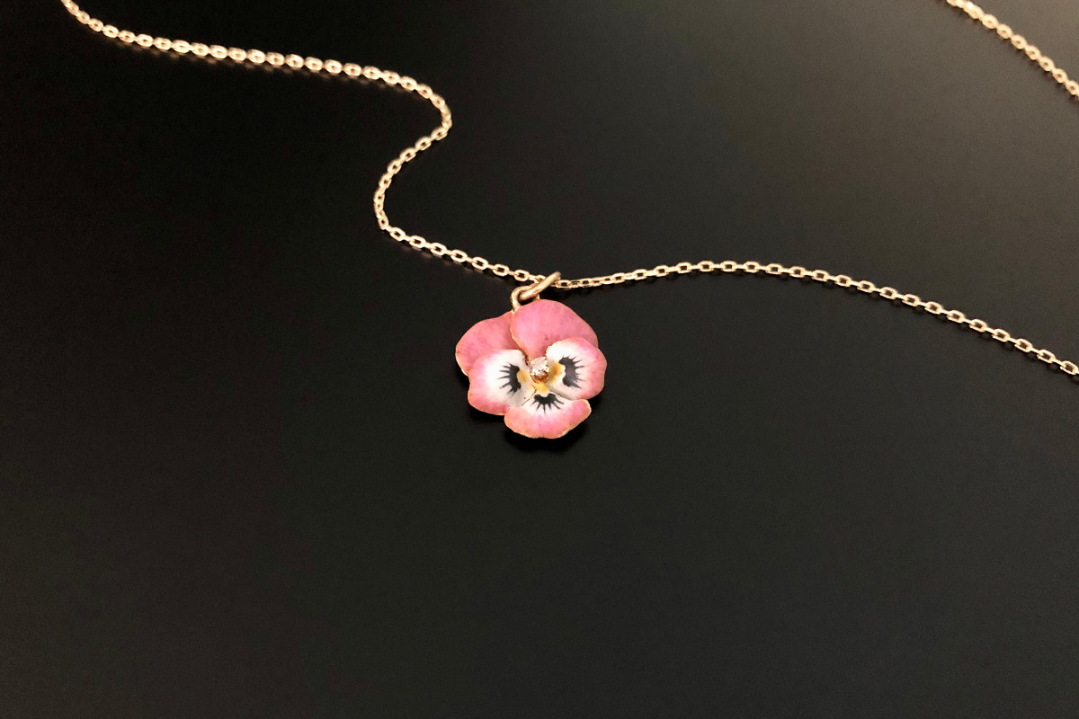 A Dainty Gold, Enamel and Diamond Pansy Pendant  Delicate petals enamelled in pink, white, yellow and black  Centrally set with a small single cut diamond 14ct yellow gold Suspended from an Italian 18ct gold trace chain Total weight: 3gms Total length: 465mm