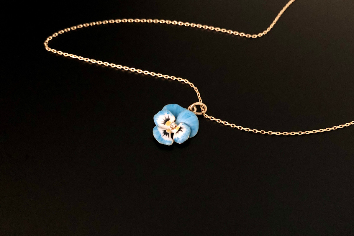 A Dainty Gold, Enamel and Diamond Pansy Pendant  Delicate petals enamelled in blue, white, yellow and black  Centrally set with a small single cut diamond 14ct yellow gold Suspended from an Italian 18ct gold trace chain Total weight: 3gms Total length: 465mm