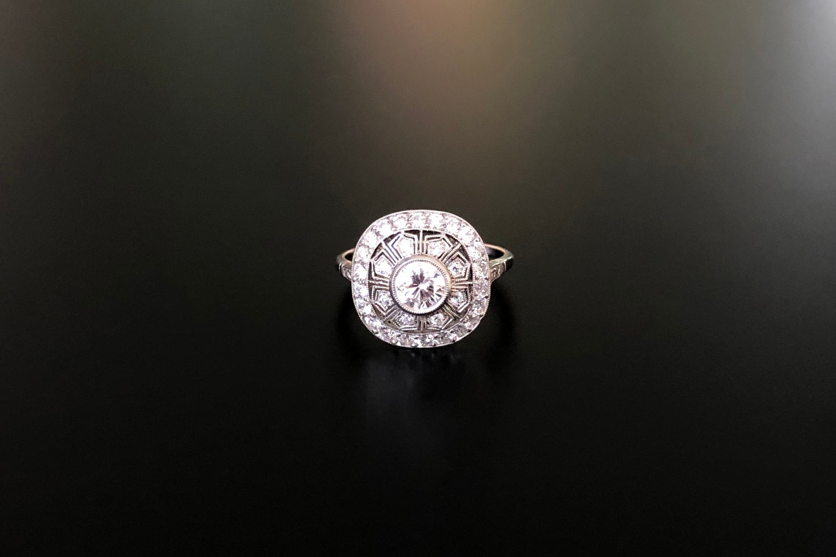 Belle Époque Style Diamond Ring Cushion shaped with finely pierced design set with a central Old European Cut diamond with radiating geometric panels, all grain set with Old Brilliant Cut diamonds. Central diamond weight: 0.58cts Approximate total diamond weight: 1.00ct. Platinum. Total weight: 4.15gms. Size: O