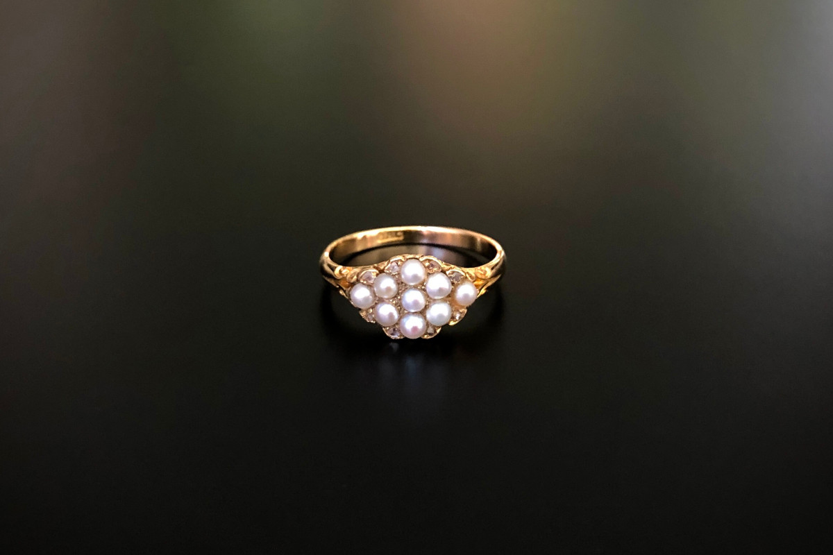 A Gorgeous Dainty Pearl and Diamond Cluster Ring Scroll setting containing nine natural half pearls set in quatrefoil formation with eight small rose cut diamonds to the border 18 carat gold setting. Total weight: 3.05gms Victorian
