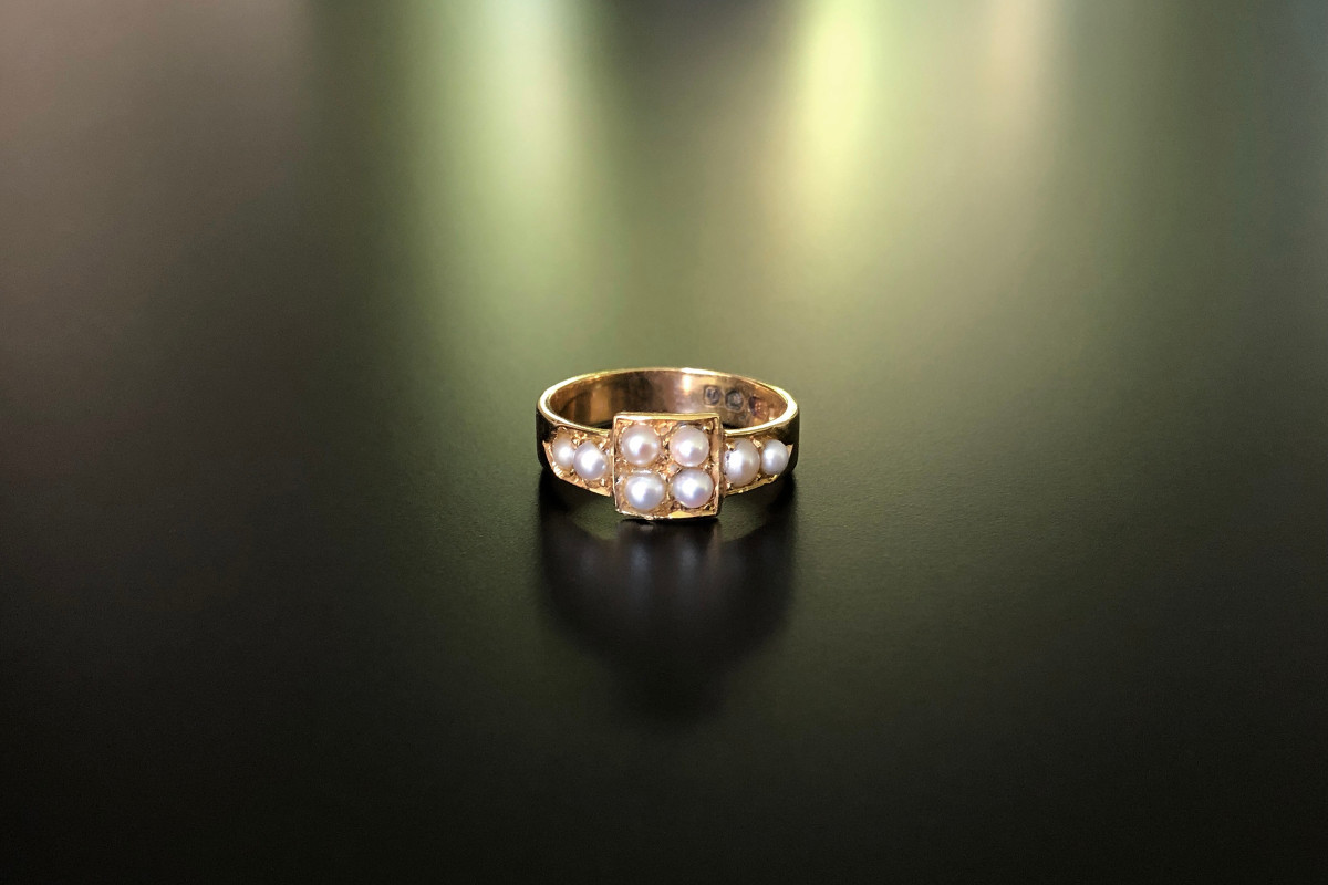 A Divine Gold and Pearl Ring Central square panel set with four seeds pearls Two further pearls set to each shoulder  18ct yellow gold Size: K1/2 Total weight: 3.35gms Victorian Circa 1870