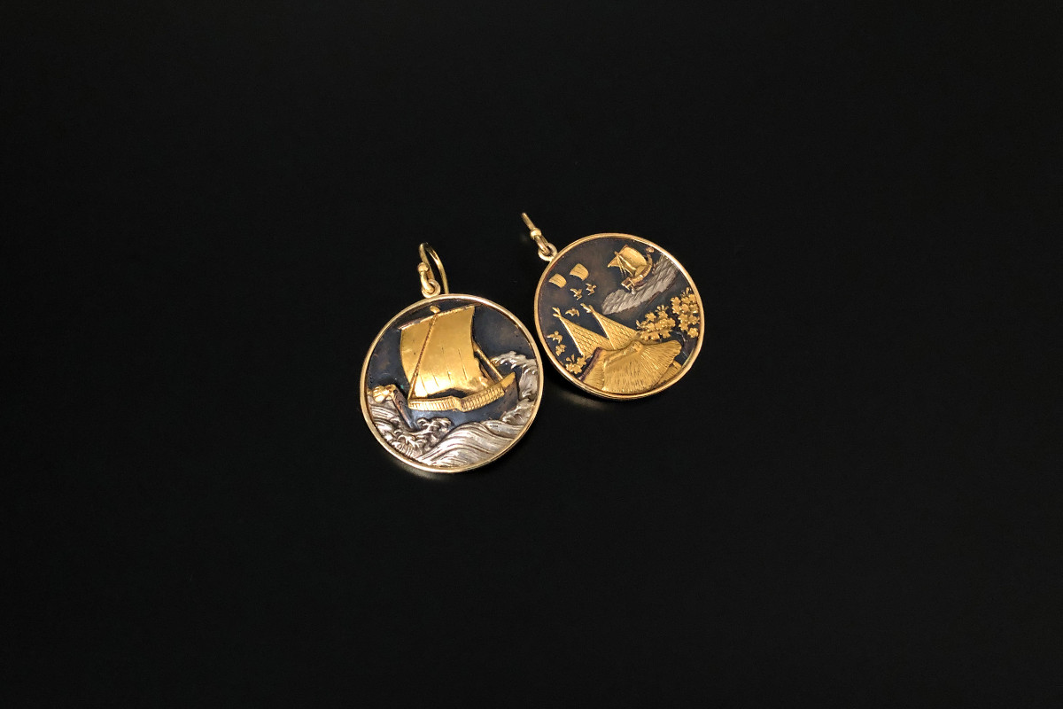 A Wonderful Pair of Shakudo Earrings Circular disc form Depicting boating scenes overlaid in gold and silver Gold backs and shepherd hook fittings 18ct gold Total weight: 12.93gms Dimensions: 25mm