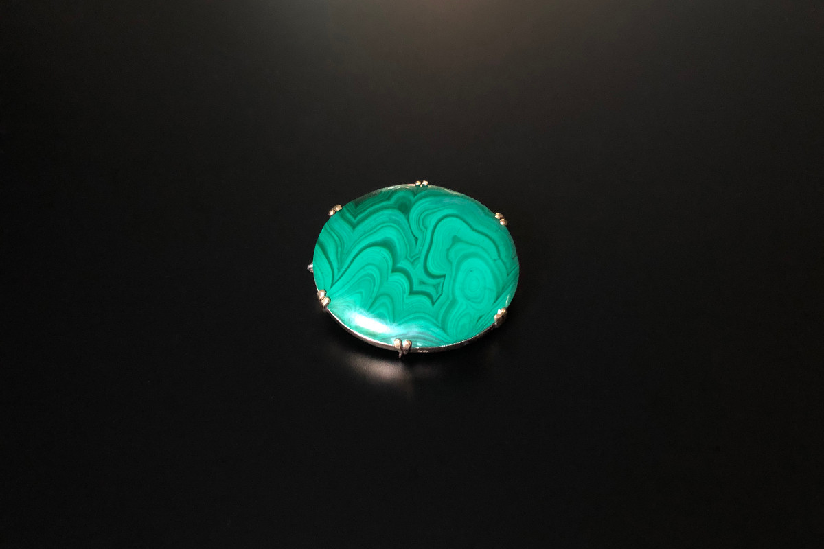 A Vibrant Australian Malachite brooch. Oval form with exquisite malachite in six double claw setting  9 carat rose gold Safety chain. Dimensions: 31 x 36mm Total weight: 26.33gms