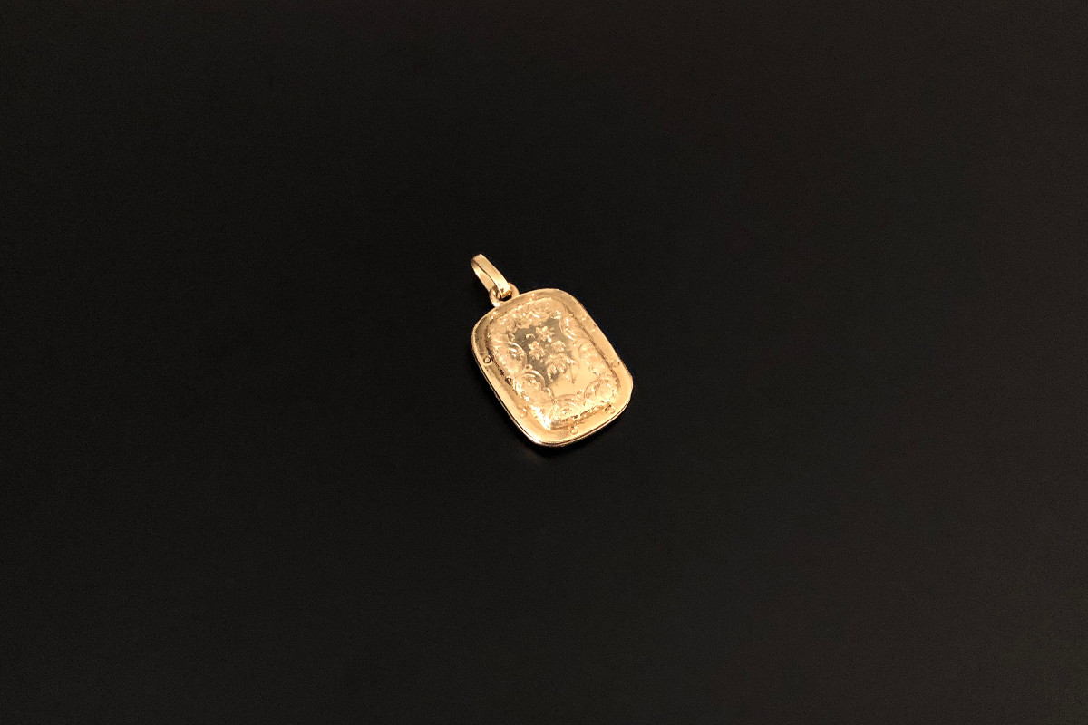 A Beautiful Miniature Locket. Cushion shape with raised central panel Engraved scroll and foliate decoration to the front and back 18 carat gold Total weight: 4.76gmsDimensions: 15 x 19mm Victorian