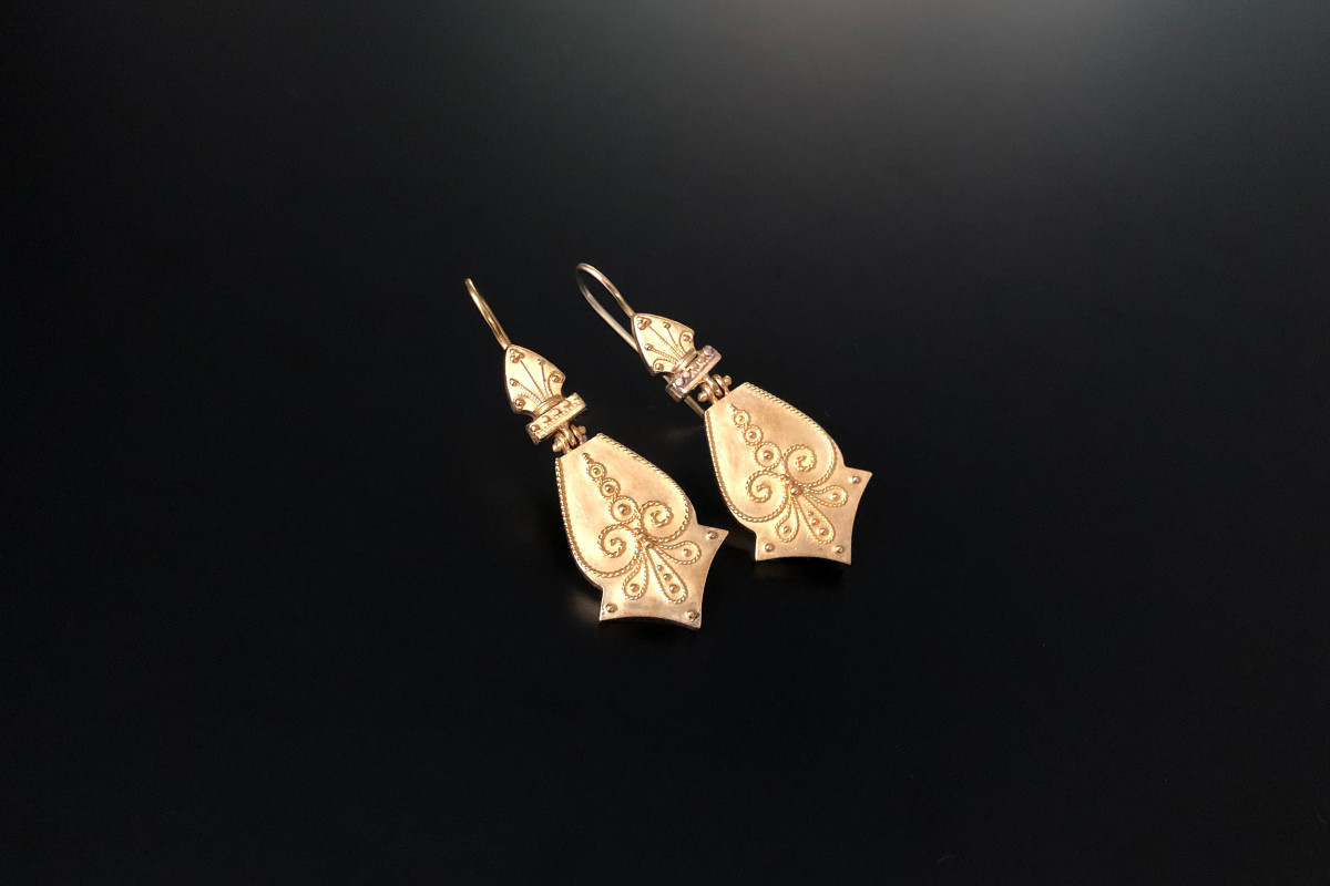 A Divine Pair of Etruscan Revival Drop Earrings Stylised mitre shaped panel with fine rope twist scroll and bead decorations, suspended from an articulated spear shaped top with further bead and rope twist design.  15ct bloomed gold. Total weight: 6.03gms Total length: 45mm Victorian.