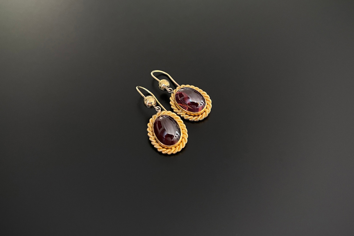 A Gorgeous Pair of Garnet Drop Earrings Oval cabochon garnet, Bezel set with rope twist frame, Suspended from ball and hook fittings. 9ct yellow gold. Total weight: 6.50gms Total length: 31mm Victorian