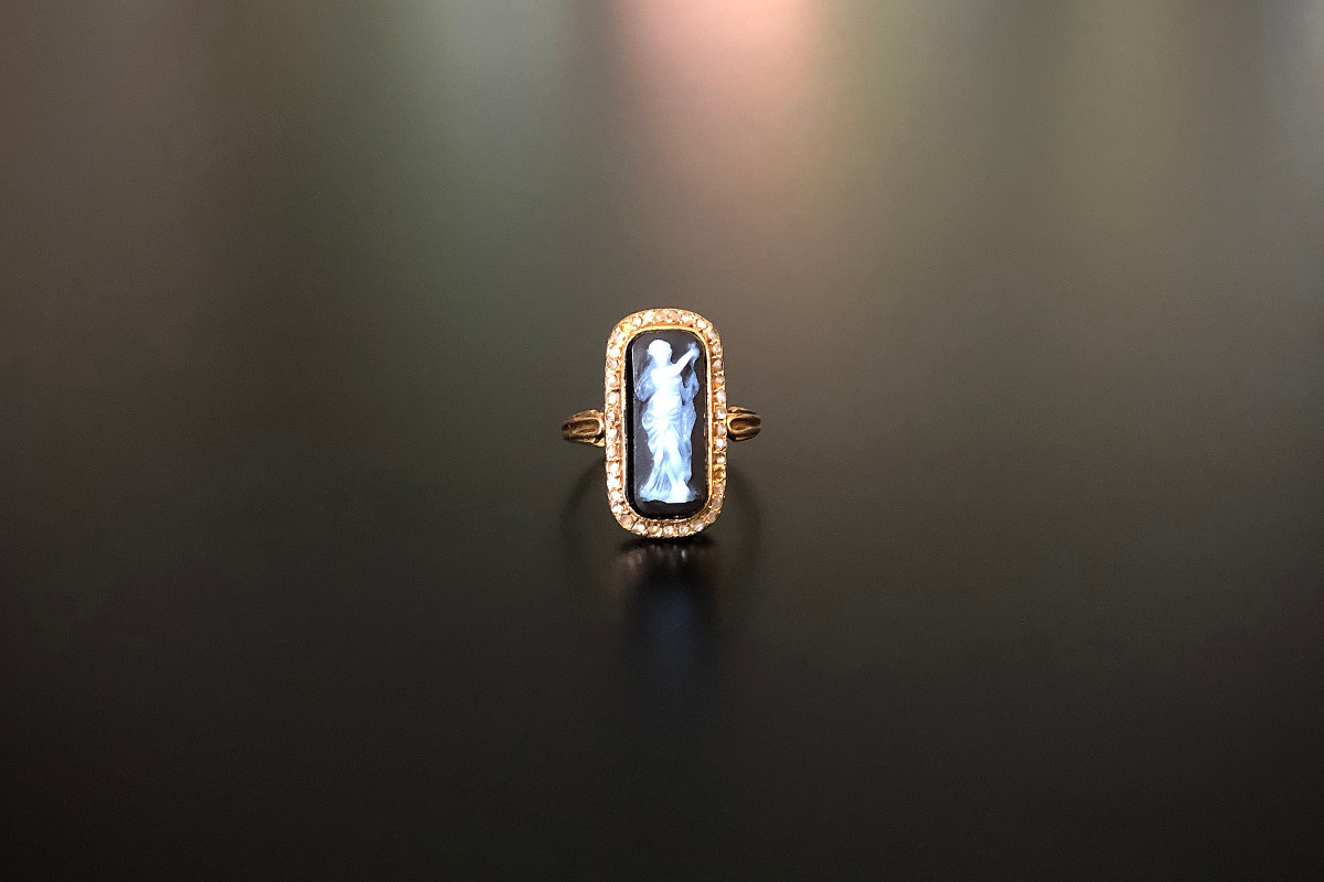 A Divine Sardonyx Intaglio and Diamond Ring Carved rectangular Sardonyx depicting a nymph,  framed by a row of rose cut diamonds. Fine bezel and millegrain setting with pierced gallery. Reeded band. 18ct yellow gold Total weight: 3.4gms