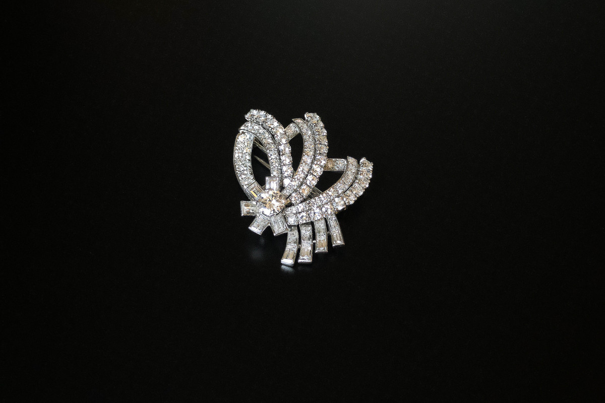 An Elegant Diamond Spray Brooch Stylised floral design consisting of a single flower set with a central brilliant cut diamond with five rectangular panels each set with a baquette cut diamond. Off set with three large navette shaped leaves set with single cut diamonds with four cascading stems set with baguette cut diamonds. Approximate central diamond weight: 0.60cts Approximate total diamond weight: 6.30 carats, approximately 34mm x 43mm c1950