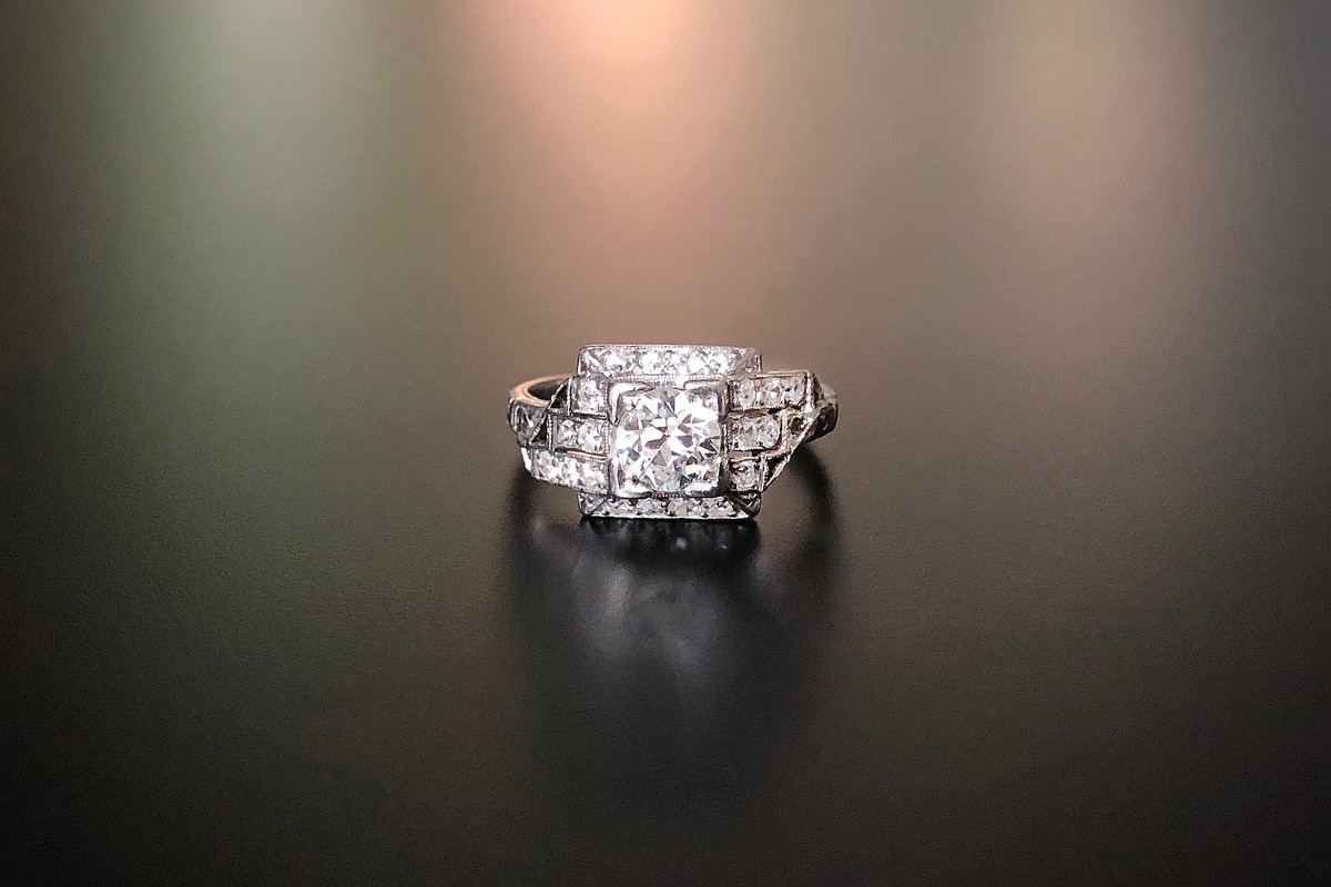 A Stylish Art Deco Diamond Ring Comprising a central Old European Cut diamond set in a square frame Surrounded by an asymmetrical step design, set with Single Cut diamonds Central diamond weight: 0.75ct Diamond colour: I Diamond clarity: VS Total diamond weight: 1.10cts Total weight: 4.07gms Platinum Size: M