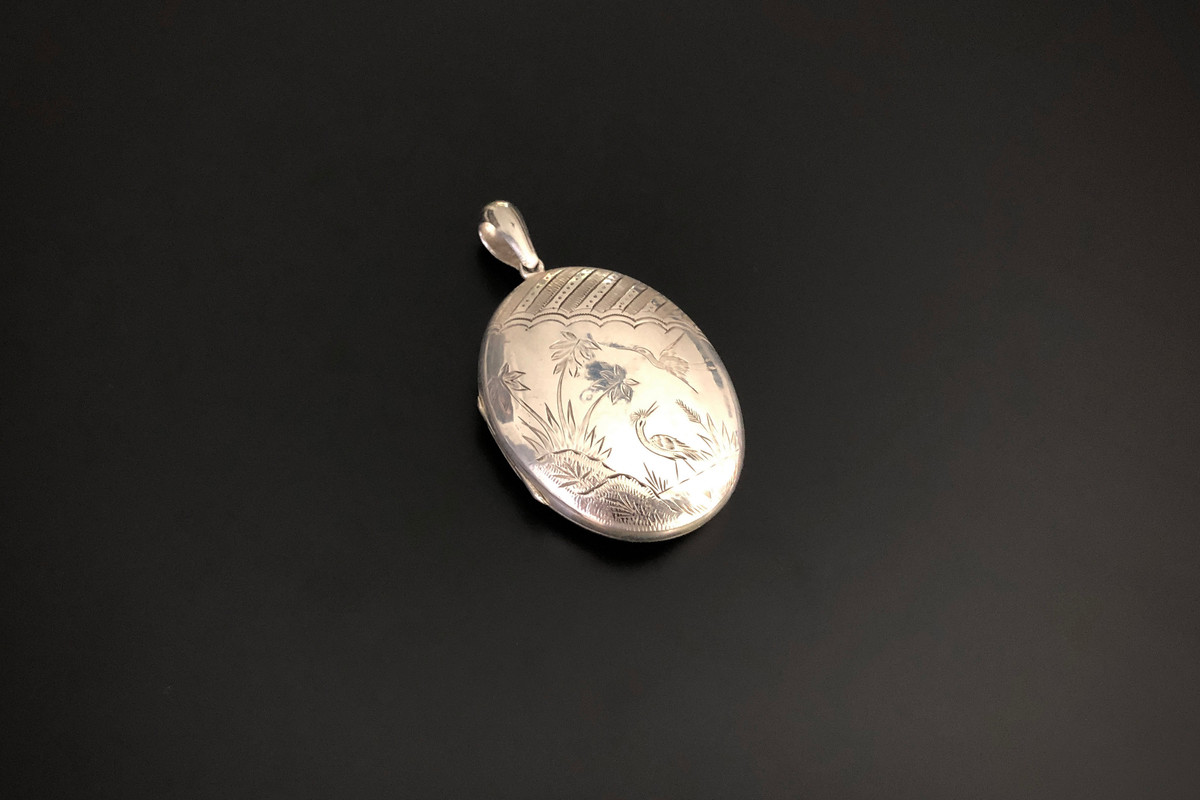 An Lovely Aesthetic Movement Silver Locket Oval form with engraved asymmetrical chinoiserie decoration depicting cranes in floral scene Sterling silver Dimensions: 52 x 40mm Total weight: 20.39gms c1910