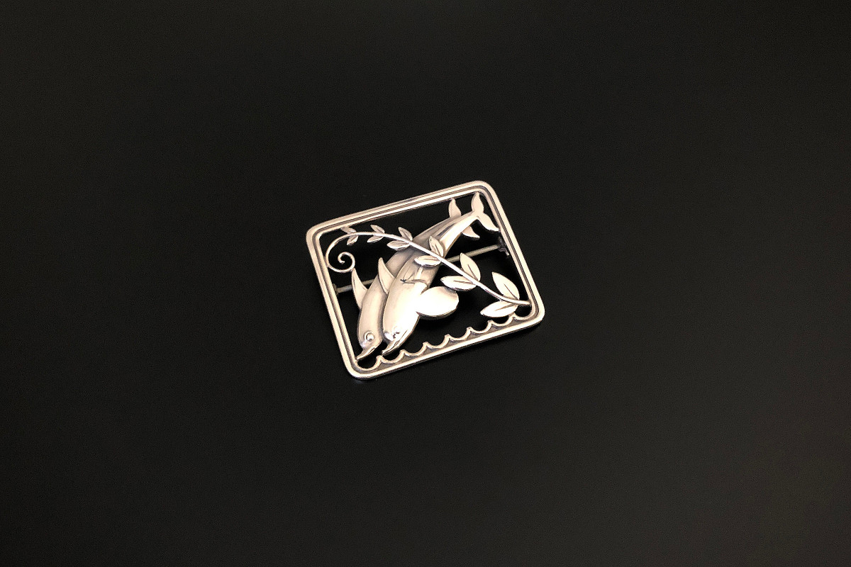 A Twin Dolphin Georg Jensen Brooch by Arno Malinowski Depicting two dolphins with leaf frond Set within a rectangular frame Sterling Silver Signed, Reference 251 London 1977 Vintage