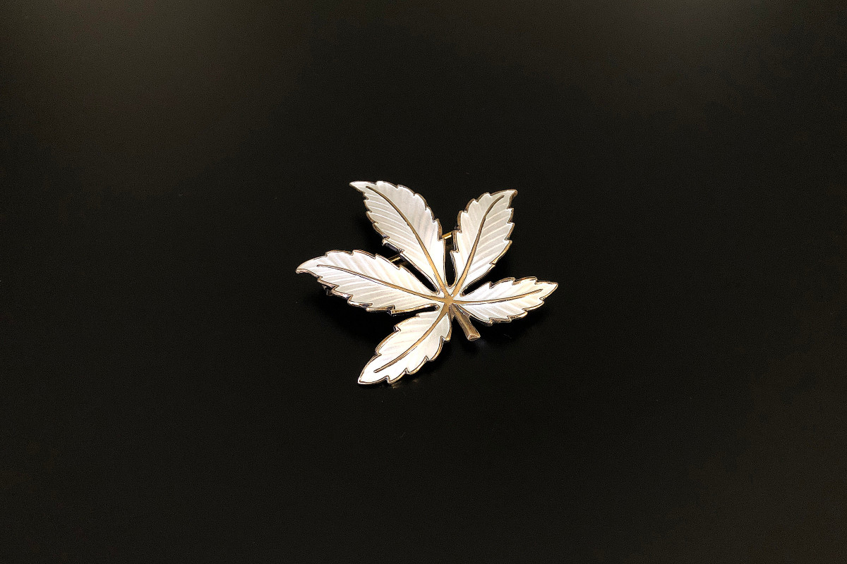 A Stylish Maple Leaf Brooch by Bernard Meldahl White enamel on silver gilt Stamped 925S Sterling Hallmarked BM Norway Total weight: 9.39gms Dimensions: 43 x 45mm Vintage